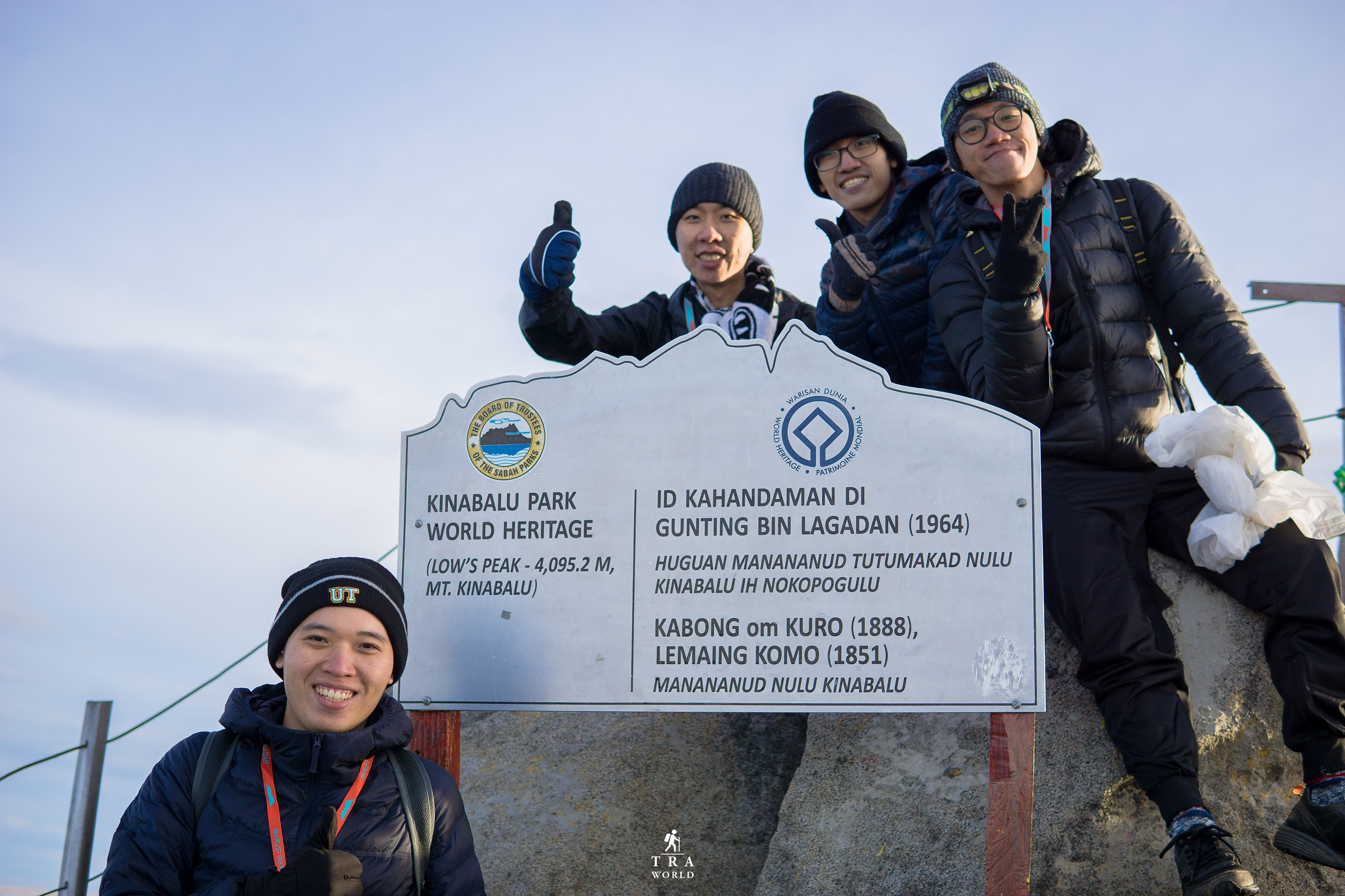 Team of accomplishing Mount Kinabalu. Mount Kinabalu peak signboard.